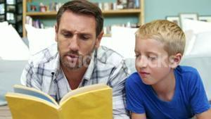 A father is reading a book to his son