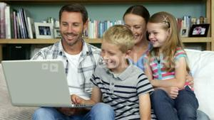 A happy family is using a computer