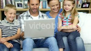 A happy family enjoying a moment with a computer