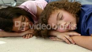 Two children are sleeping on the floor
