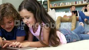 Two children are using computer while parents are using pad