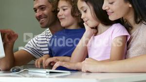 Happy family smiling and using a computer together