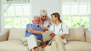 Nurse doing a health check up with mature man on a sofa