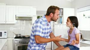 Father telling off his daughter on the kitchen
