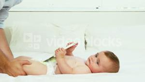 Happy father playing with his baby on a bed