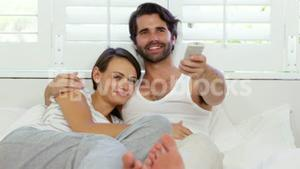 Cute couple lying on a bed and looking the television