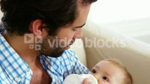 Close up of happy father bottle feeding to his baby