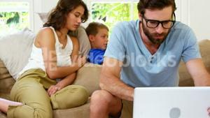 Concentrated father in front of mother and son sitting on a sofa