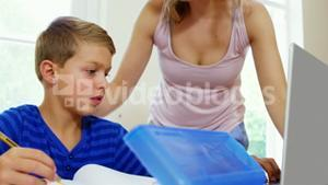 Mother helping his son to use computer
