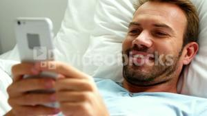 A man is texting in his bed