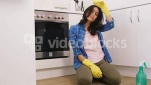 Tired woman sitting on the floor during the cleaning