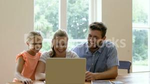 A family of three is using laptop
