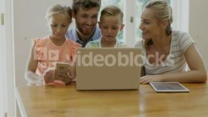 Portrait of happy family using technology