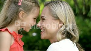Portrait of cute mother and daughter embracing and smiling
