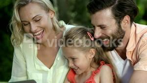 Portrait of cute family are looking a laptop and smiling