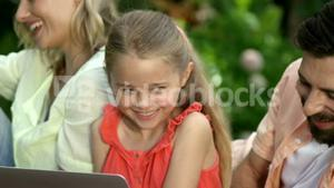 Portrait of cute family are sitting on the grass and using electronic devices