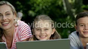 Portrait of cute family are lying on the grass and using electronic devices