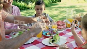 Happy family is eating together in the garden