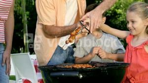 Close up on happy family is eating a barbecue in the garden