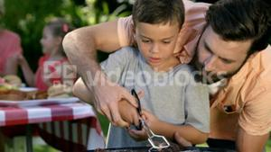 Close up on a father is teaching to his son to do a barbecue
