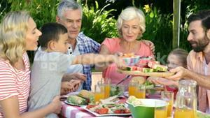 Multi-generation family is eating in the garden