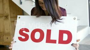 Woman holding billboard which is written SOLD