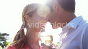 Happy couple romancing while having a glass of wine in field