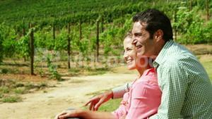 Happy couple interacting while sitting in field