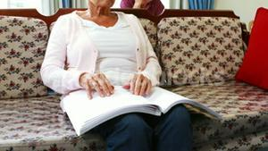 Senior woman reading book in braille