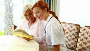 Nurse and old woman reading book together