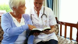 Senior woman and nurse reading a book together