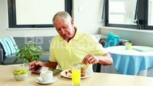 Retired man using tablet while eating breakfast