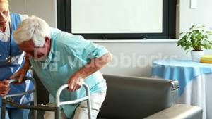 Nurse helping retired man with walker