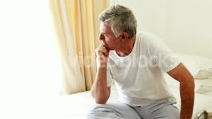 A senior man thinking while looking through window