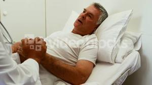 Doctor visiting patient and holding hands