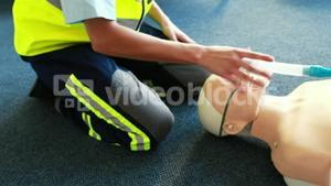 Woman exercising her first aid on a model