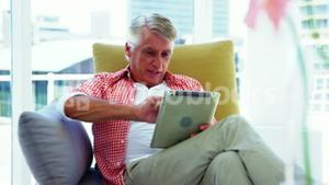 Mature man sitting on sofa and using digital tablet in living room