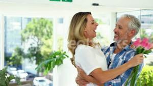 Mature man giving a bunch of roses to woman