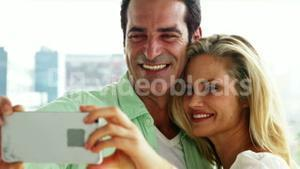 Smiling couple taking a selfie from mobile phone in living room at home