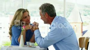 Smiling mature couple interacting in living room at home