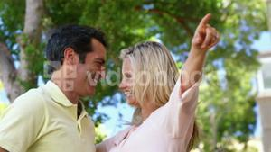 Smiling couple pointing on a sunny day