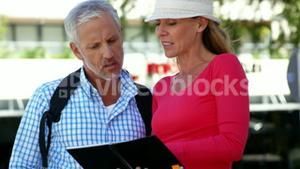 Mature couple is looking a book in the street