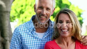 Mature couple is smiling and posing in front of the camera