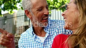 Mature couple is sitting in the street and laughing