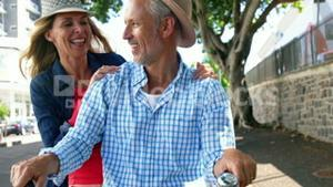 Portrait of mature couple is smiling and is on the same bike