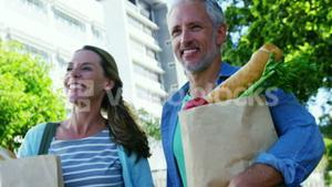 Mature couple is walking on the street with groceries