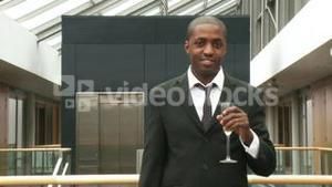 Ethnic businessman drinking champagne in office