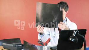Male doctor using a laptop and studying an xray footage