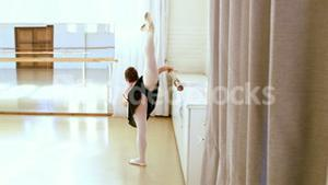 Ballerina from the back is doing exercises with a bar