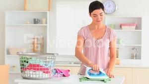 Smiling housewife ironing clothes